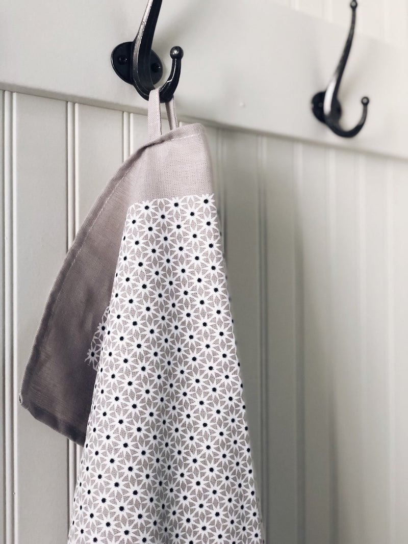 A closeup of a grey starburst tea towel hanging on a black hook against a white wooden wall