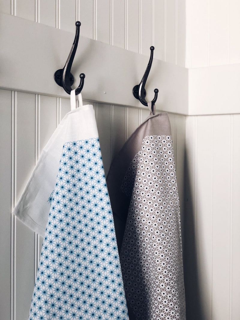 Grey & blue starburst tea towels hanging on black hooks against a white wooden wall