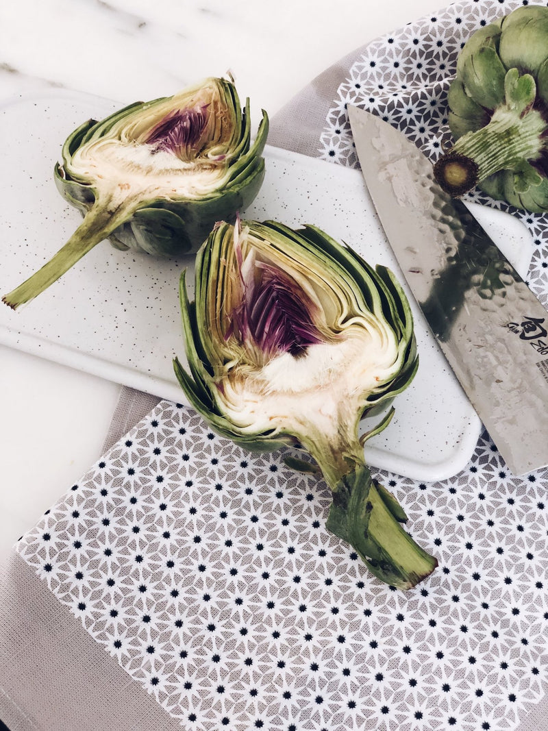 A grey starburst tea towel laying on a white marble counter with a white speckled ceramic serving dish, large knife and slices of artichokes laying on top