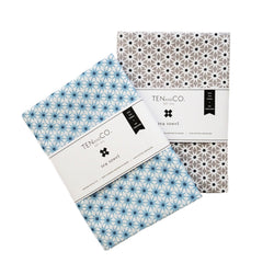 Two folded cotton-linen blend tea towels with grey and blue starburst prints with a white paper labels securing them