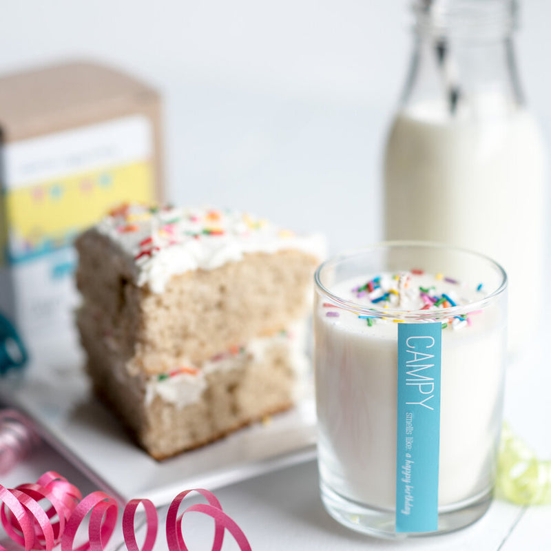 Happy Birthday candle next to a slice of vanilla cake with sprinkles, ribbon and a bottle of milk with a paper straw