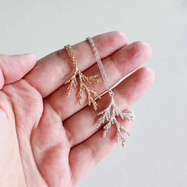 Someone holding two silver and gold-plated juniper branch necklaces in their hand