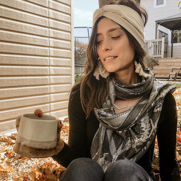 A woman wearing a Khaki Bohemian Headband, macrame earrings, a grey scarf, a black long sleeve and black jeans looking into her clay coffee mug while sitting in a pile of fall leaves
