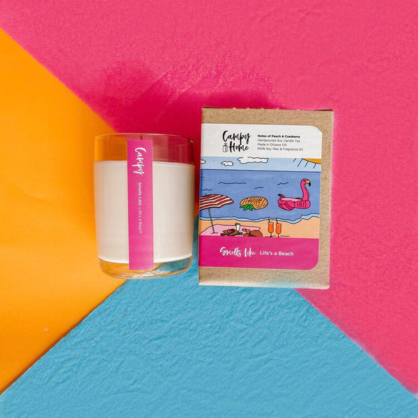 Life's a Beach candle flat lay next to the box on a multicolour background