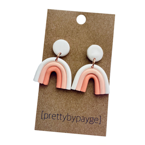 "A pair of peach toned clay rainbow arch earrings with brass rings attached to a tan paper card labeled ""Pretty by Payge"" on a white background"