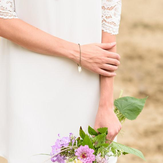 A woman in a white lace dress walking through a field holding flowers while wearing a raw crystal bracelet