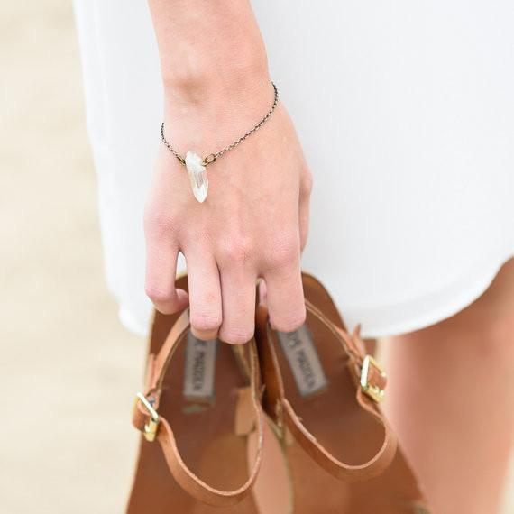 A woman walking on the beach in a white sundress carrying her tan leather strappy sandals while wearing a raw crystal bracelet