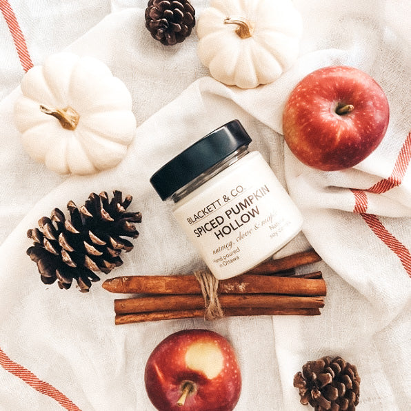 Spiced pumpkin hollow jar candle laid on its side on a red and white striped cloth with various mini white pumpkins, red apples, pinecones and a bundle of cinnamon sticks scattered