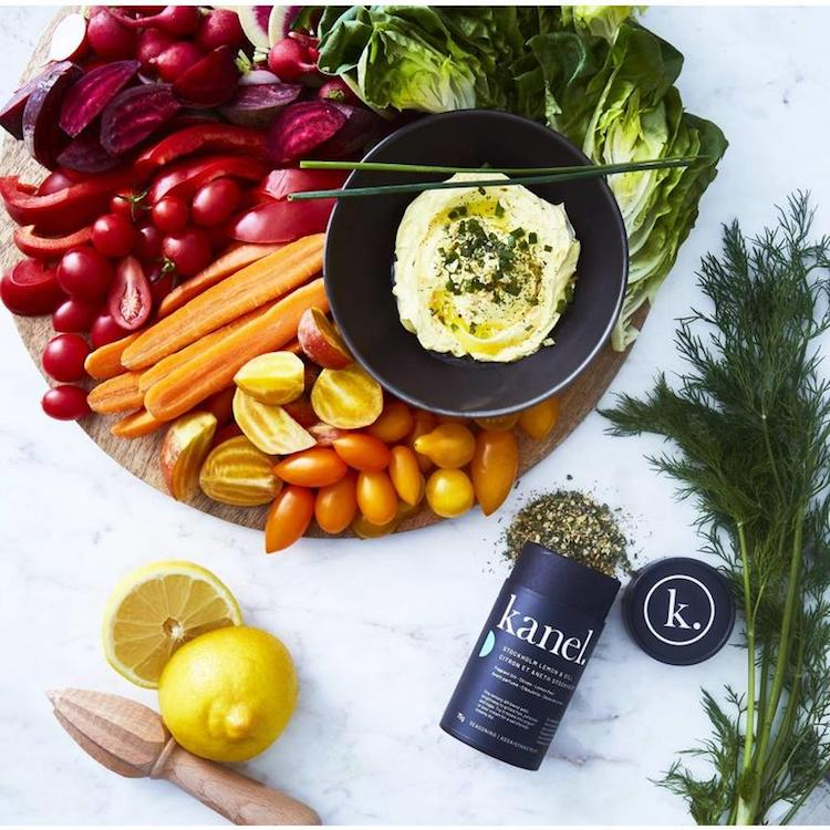 A wooden cutting board covered with various vegetables and a bowl of yogurt dip sprinkled with Stockholm Lemon & Dill spice next to a tube of Lemon & Dill spice with spices pouring out