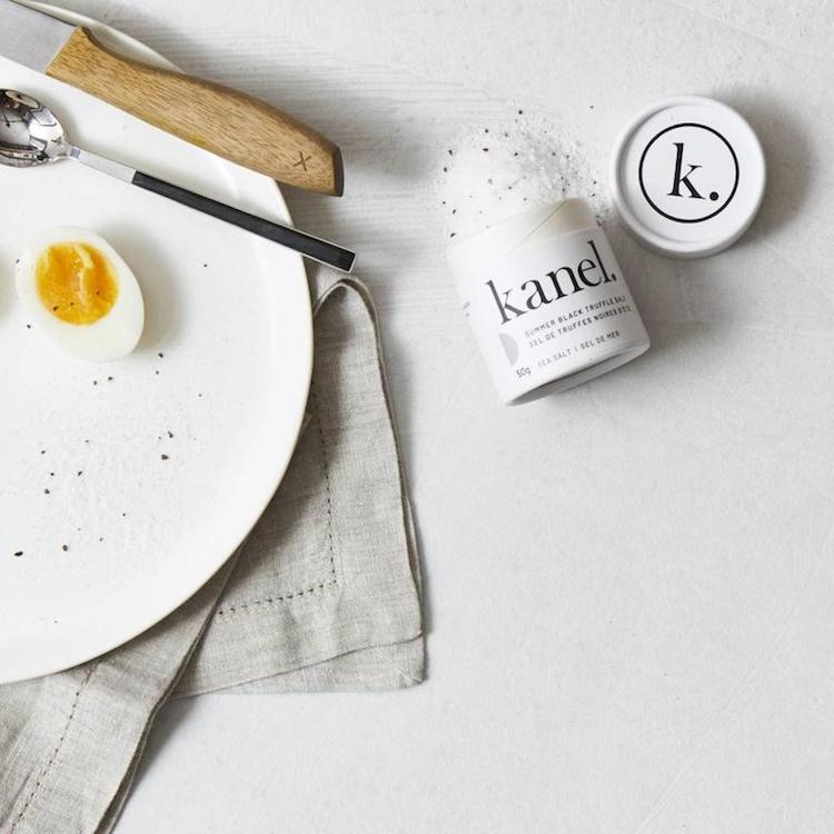 A white plate with half a hard boiled egg next to a tube of Summer Black Truffle Salt with spices pouring out