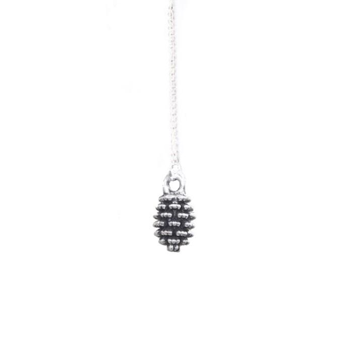 Silver-plated pinecone necklace hanging in front of a white backdrop