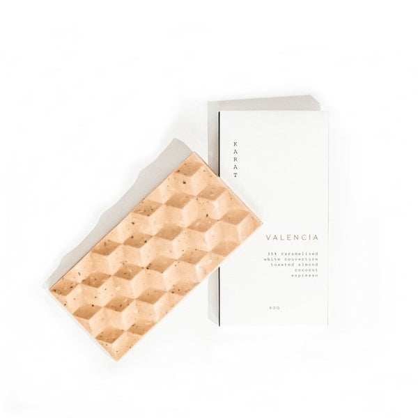 A geometric caramelized white chocolate bar with real Italian espresso laying next to a white and silver Valencia bar box