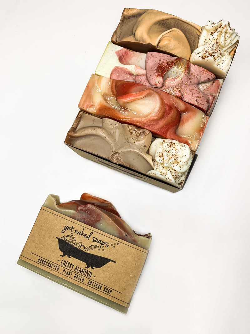 Various small batch hand poured soaps side-by-side with a cherry almond soap featured