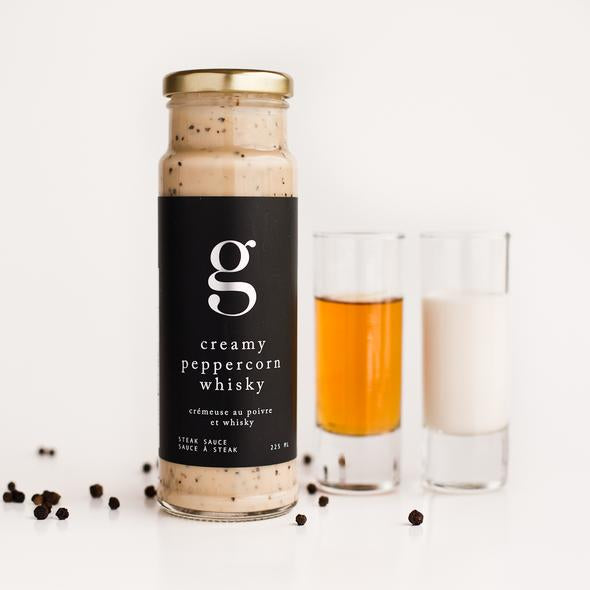A bottle of Creamy Peppercorn Whisky Steak Sauce next to a shot glass of whisky and a shot glass of cream with individual peppercorns scattered around