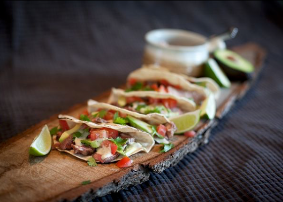 Steak and pepper tacos laid side by side next to a bowl of Creamy Peppercorn Whisky Steak Sauce and a side of limes and avocado on a live edge wooden plank
