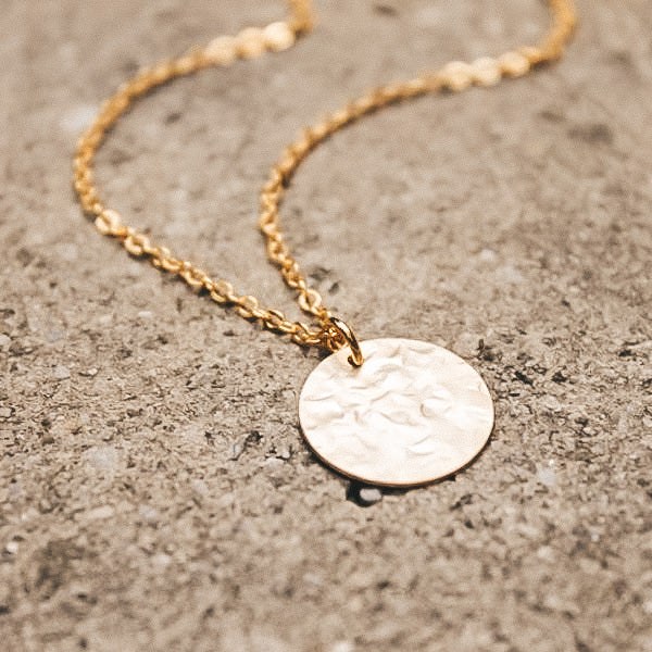 A close up of a 16K gold-plated hammered disc necklace attached to a gold chain laying on concrete