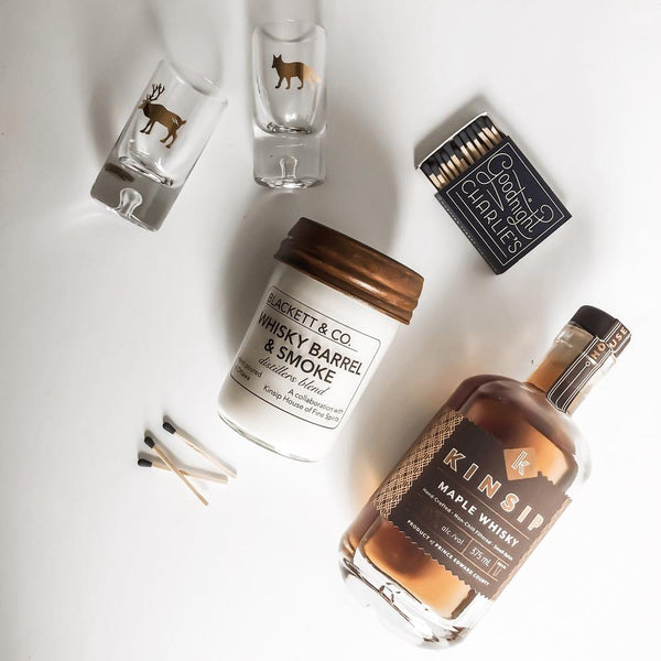 A whisky & smoke jar candle laid on its side next to two shot glasses, a small box of matches and a bottle of Kinsip Maple Whisky