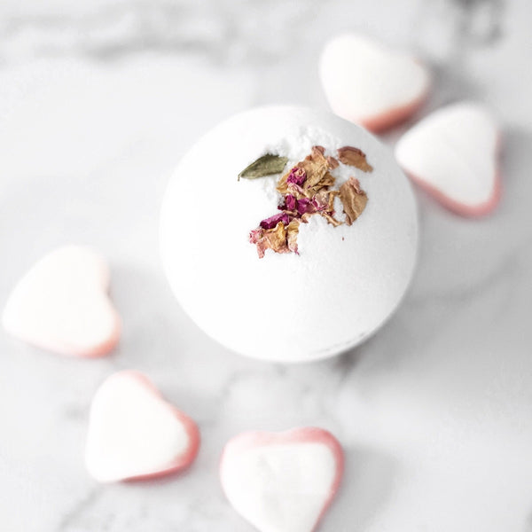 A Sweet Vanilla Buttercream bath bomb laying on a marble table surrounding by pink and white bath bomb hearts