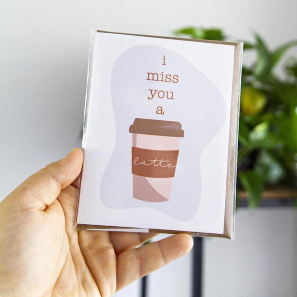 "Someone holding a 4.25"" x 5.5""  matte white card with ""I miss you a latte"" over top a picture of a latte laying on top of a kraft envelope incased in a cellophane sleeve with a green plant in the background in front of a grey wall"