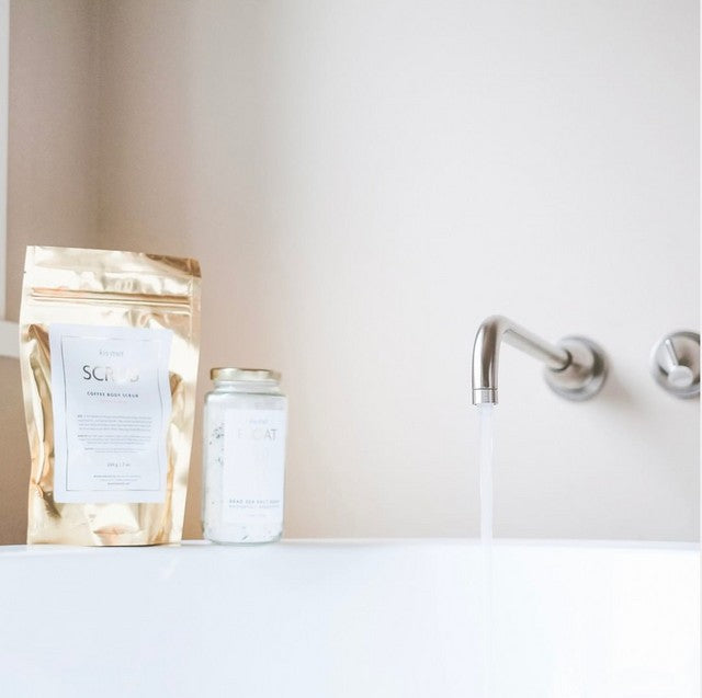 Water from a faucet pouring into a neutral white bathtub with a gold bag of Kismet coffee scrub and a clear bottle of white bath salts sitting on the edge of the tub