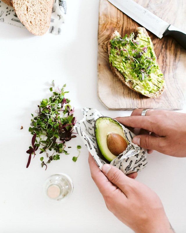 A woman wrapping an avocado half in a small white beeswax wrap alongside her alfalfa sprout sandwich