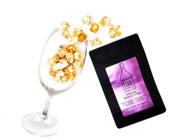 Poppin' Merlot PB&J Popcorn bag next to flat lay of popcorn in a wine glass