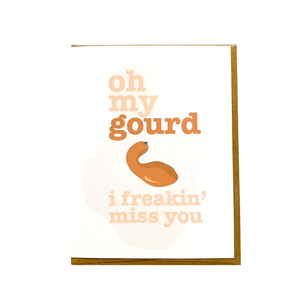 "A 4.25"" x 5.5""  matte white card with ""oh my gourd I freakin' miss you"" over top a picture of a gourd laying on top of a kraft envelope incased in a cellophane sleeve"
