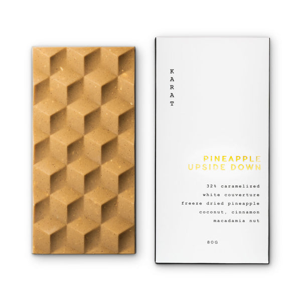 A geometric caramelized chocolate bar with freeze dried pineapple and toasted coconut laying side-by-side next to a white and gold Pineapple Upside Down bar box