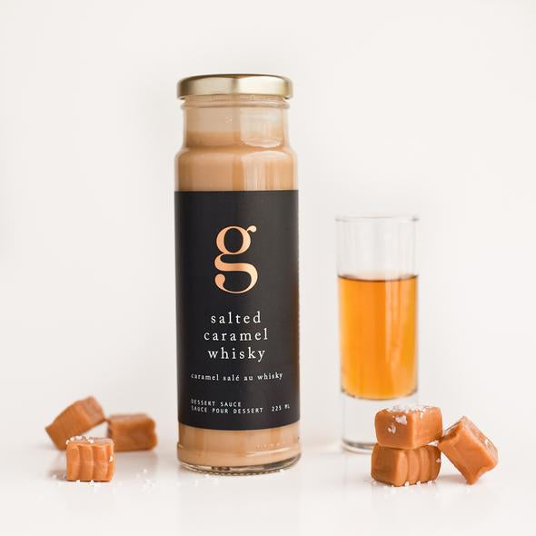 A bottle of Salted Caramel Whisky Dessert Sauce next to a shot glass of whisky with individual salted caramels surrounding them