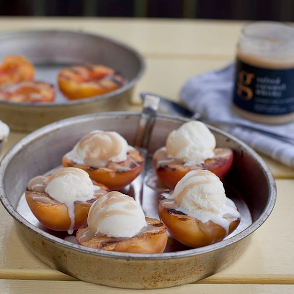 Salted Caramel Whisky Dessert Sauce poured over grilled peaches filled with vanilla ice cream