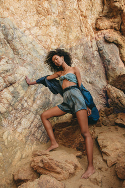 model standing leaning against beach rocks wearing large silk scarf as a top in color aquamarine blue green