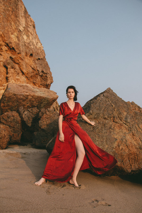 model standing on beach in front of rocks wearing muted red silk wrap dress