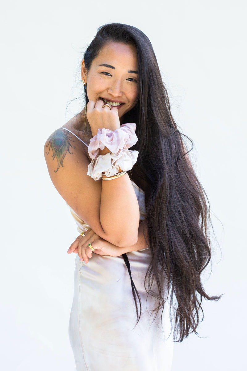 model smiling wearing two silk scrunchies on arm