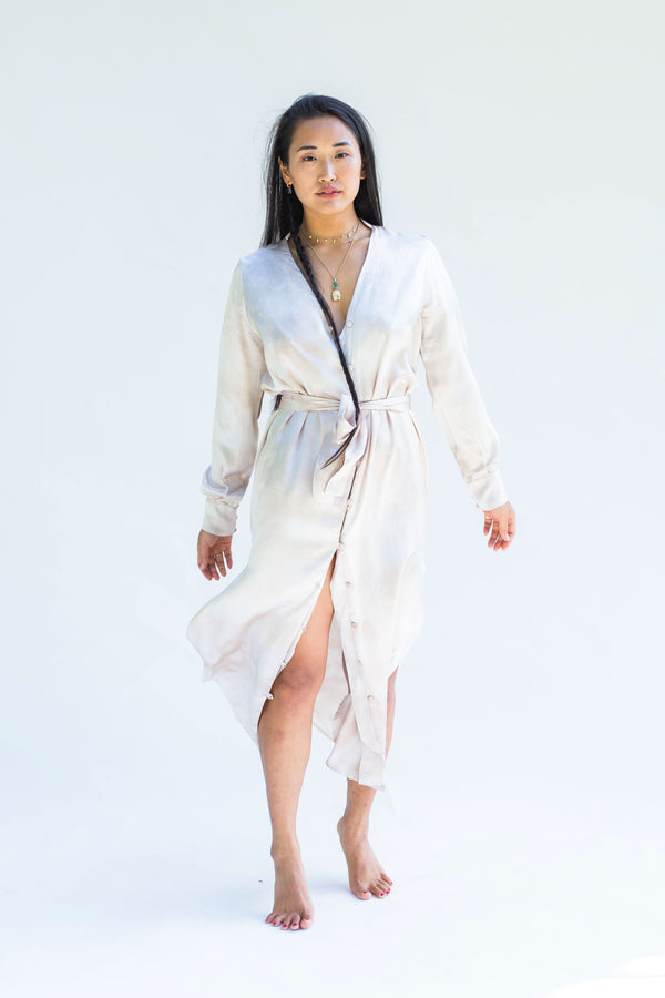 model wearing button down silk dress in cream beige color with silver undertone