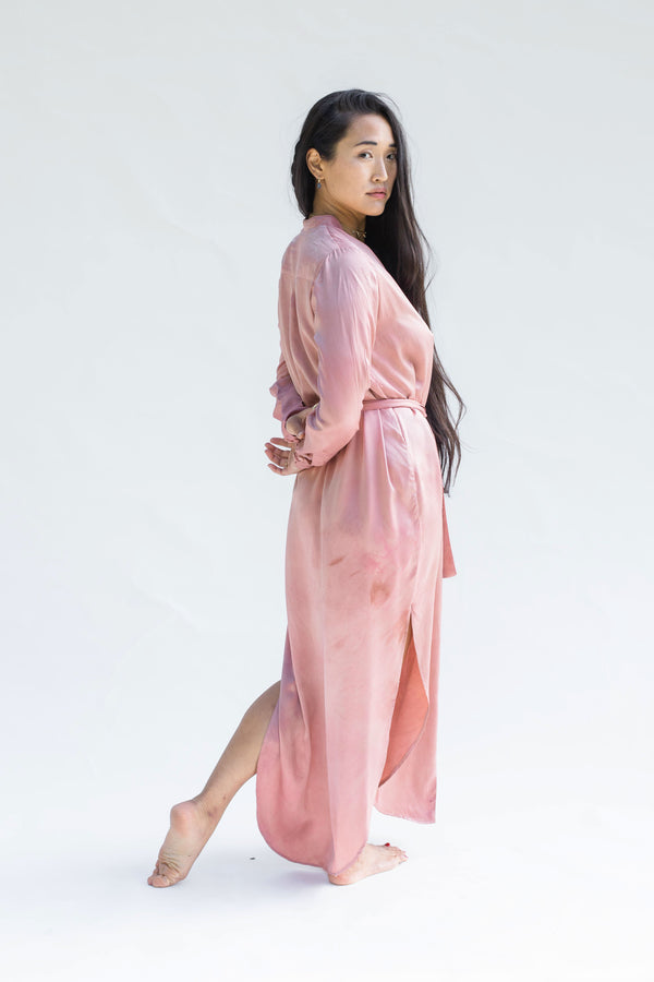 model turned to the side wearing button down silk dress in muted pink