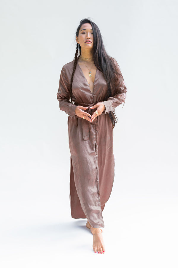 model walking with hands together wearing silk button dress in muted berry brown