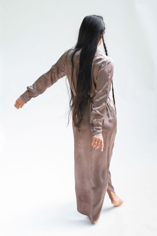 model swinging arms showing back of model walking with hands together wearing silk button dress in muted berry brown
