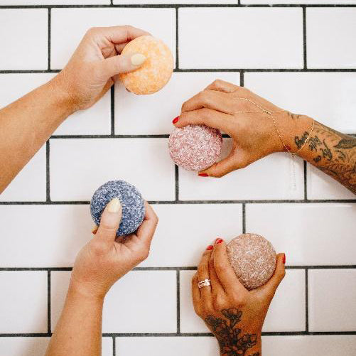 two peoples hands holding shampoo bars in front of a tiled wall