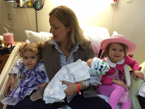 Emily holding new baby with big sisters