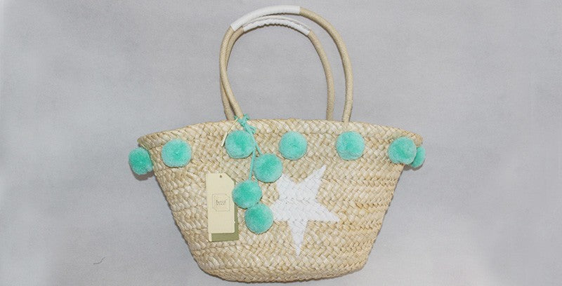 straw tote with pom poms