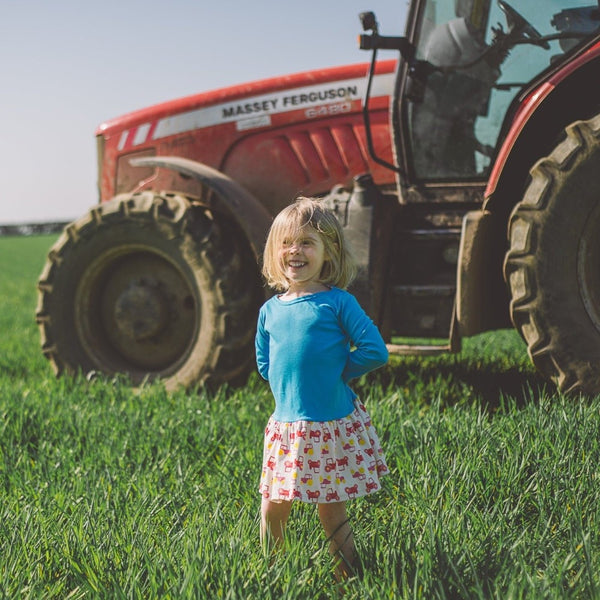 girl wearing Bright Blue Tractor Long Sleeved Dress by Toucan Blue | Cotswold Baby Co