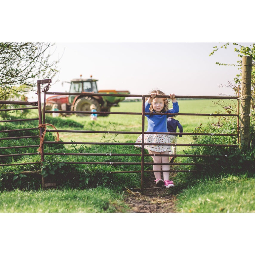 little girl wearing farmyard dress by Toucan Blue | Cotswold Baby Co
