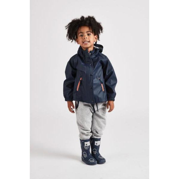 Little boy wearing a navy waterproof rain cheater coat by grass and air, Cotswold Baby Co