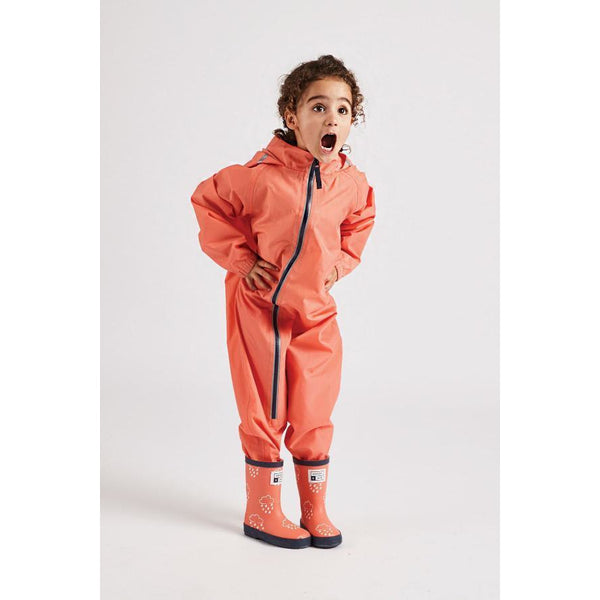 Little girl wearing coral stomper suit by grass and air - Cotswold Baby Co