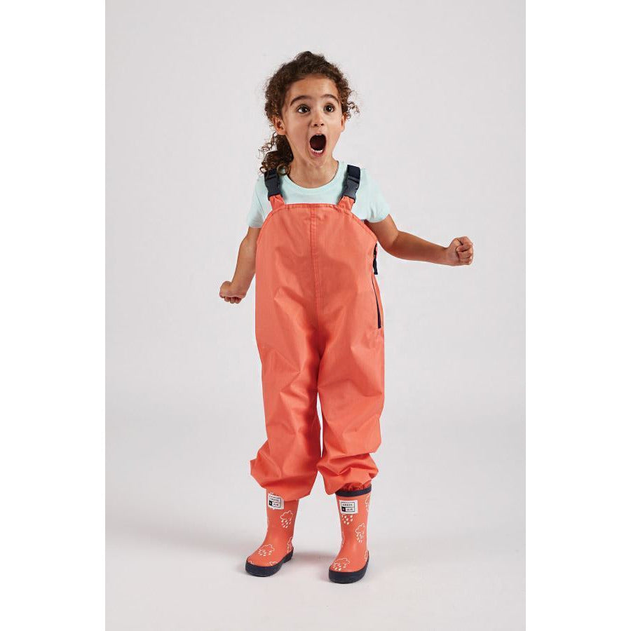 girl wearing coral waterproof dungarees by Grass & Air - Cotswold Baby Co