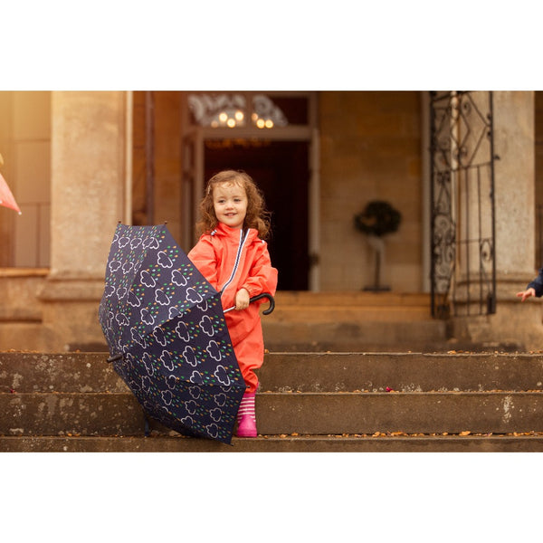 little girl holding colour changing umbrella - grass and air