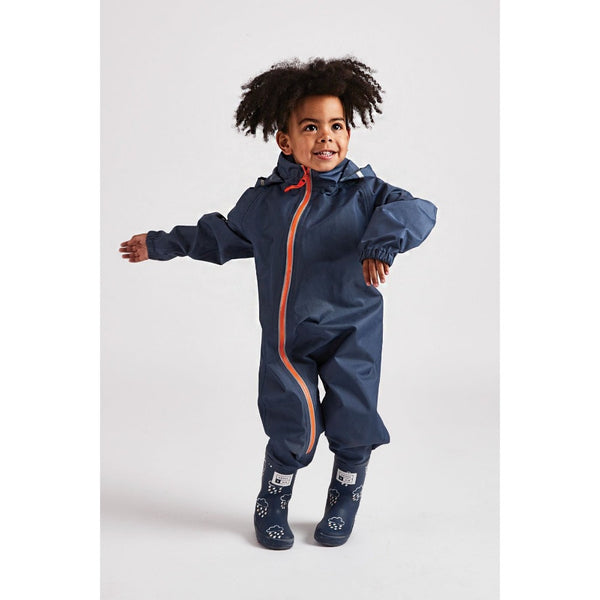 Little boy wearing navy waterproof stomper suit by grass and air - Cotswold Baby Co