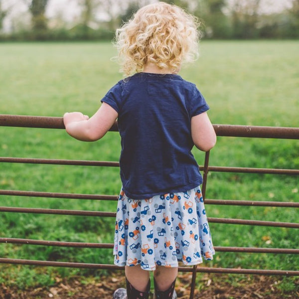 little girl wearing pastel blue tractor skirt by Toucan Blue | Cotswold Baby Co