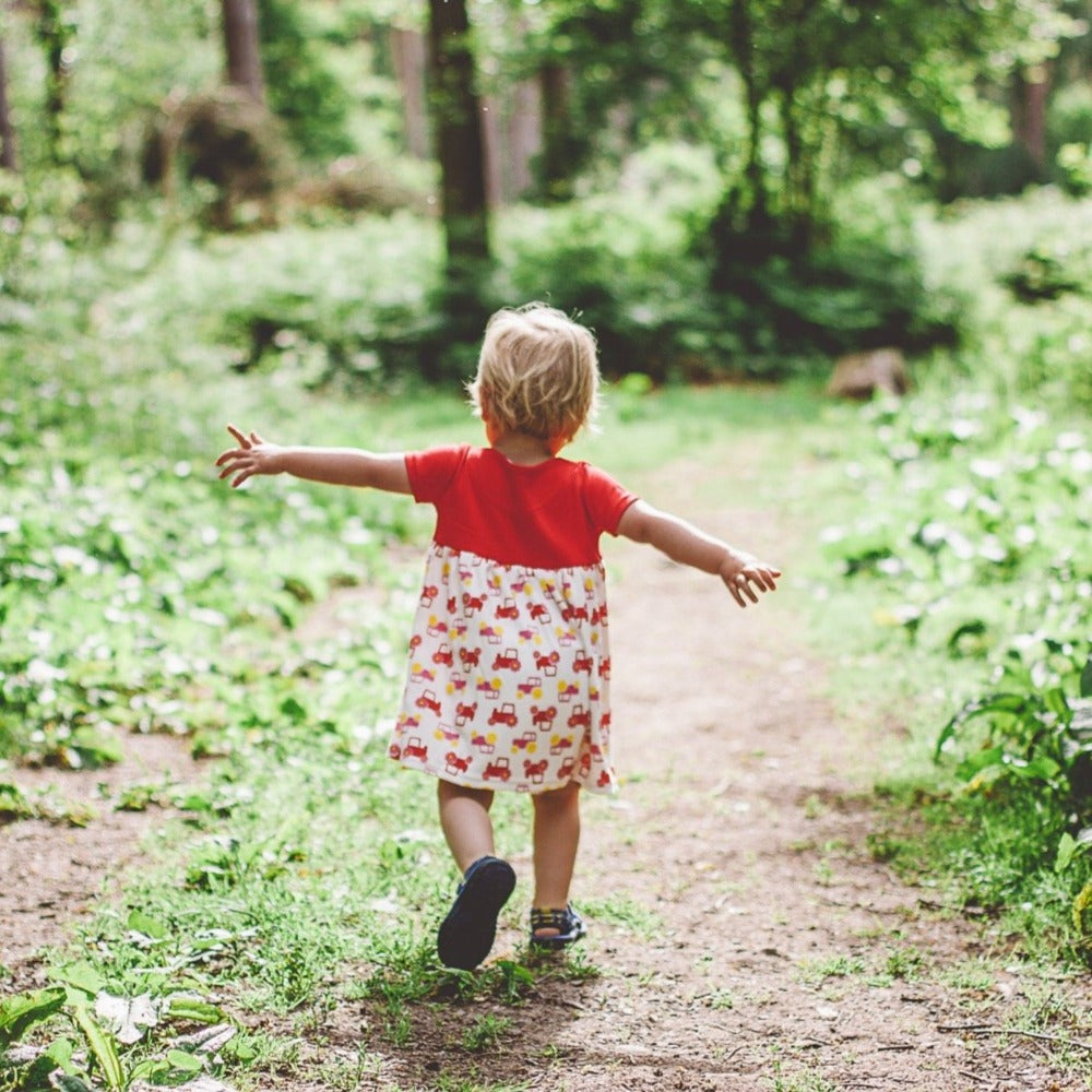 little girl in woods wearing red short sleeve tractor dress from toucan blue | Cotswold Baby Co