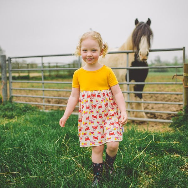 little girl wearing yellow tractor dress by Toucan Blue | Cotswold Baby Co